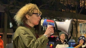 A person with long curly hair and glasses speaks into a megaphone
