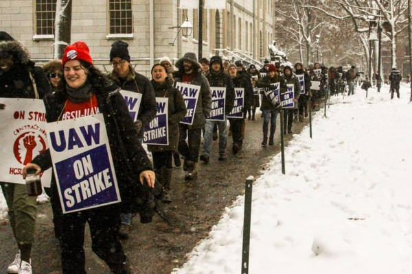 A line of Grad students and their allies march through Harvard Yard in the snow holding