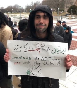 "Man holds sign that says ""Iranians no NOT want a war with the U.S.A."""