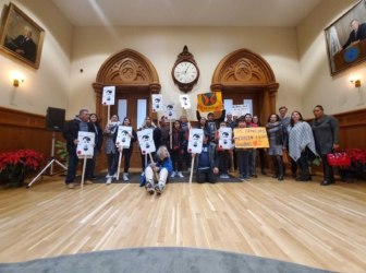 Protesters stand and sit with signs on a wooden floor.