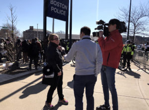 A woman speaks to two news reporters on the edge of a rally.