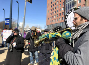 A protest band plays brass instruments at an outdoor rally, bundled in winter clothes.