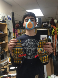 A young man wears a 3d printed face mask and holds two hand sewn masks