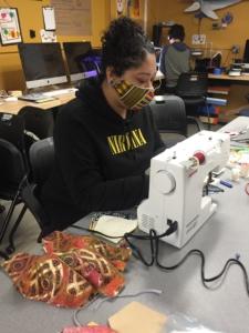 a volunteer sews olsen masks at a sewing machine.
