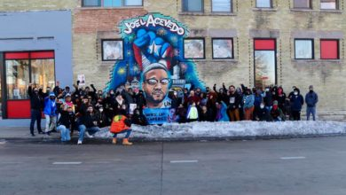 Protesters stand in front of a mural to Joel Acevedo, who was killed by an off-duty police officer in Milwaukee. Liberation photo