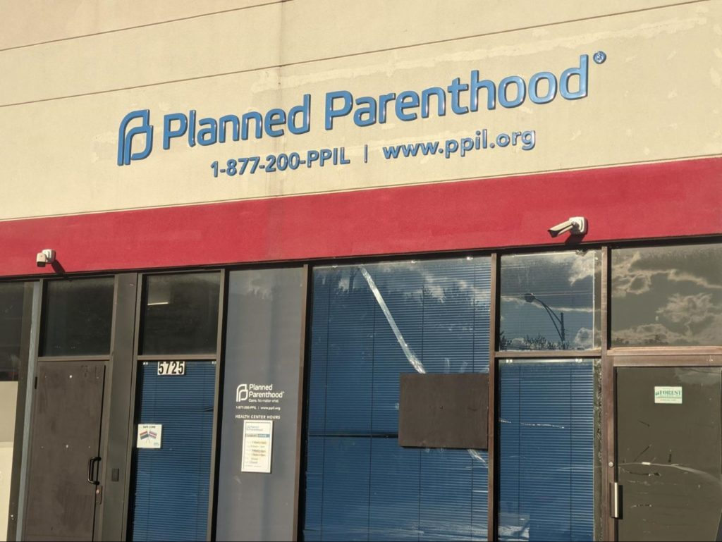 Board and tape cover up broken glass after a Planned Parenthood clinic in Chicago was vandalized earlier this week. Liberation photo