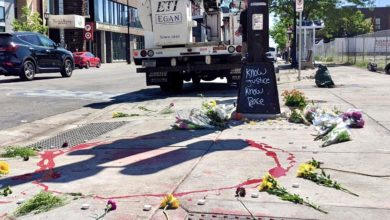 """A circle of red paint surrounds dried blood from a fatal attack on protesters in Minneapolis. Street art on a lamppost at the scene reads """"know justice, know peace."""" Liberation photo"""