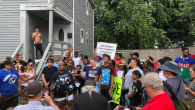A large crowd gathers outside a grey house on Sayles Street. There are many microphones and media present. People hold signs.