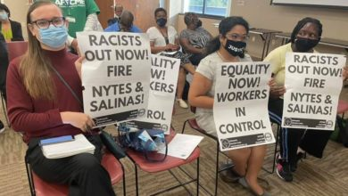 Protesters holding placards at the July 26 Indianapolis Public Library Board meeting. Liberation photo