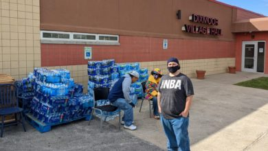 Volunteers distribute bottled water in front of Dixmoor Village Hall on October 22, 2021 Liberation photo