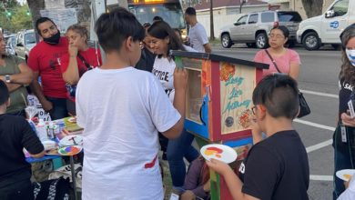 """Children help paint the little library, which was designed by PSL member Naomi Powers, and features designs of Anthony, his favorite soccer team Club Universidad Nacional, flowers and the text """"Long Live Anthony."""" Liberation photo"""